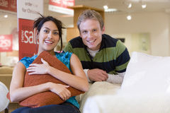 Young couple in shop, woman on sofa, smiling, portrait Royalty Free Stock Photos