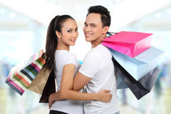 Young couple shopping. Romantic young couple shopping in the mall with many shopping bags Stock Images