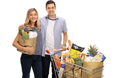 Young couple with a shopping bag and a cart filled with grocerie. S isolated on white background Stock Photography