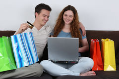 Young couple with shopping bags doing internet shopping Royalty Free Stock Photo