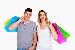 Young couple with shopping bags in front of white background. Happy young couple with shopping bags in front of white background Stock Photo