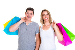 Young couple with shopping bags in front of white background. Happy young couple with shopping bags in front of white background Royalty Free Stock Images