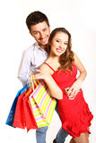 Young couple with shopping bags hugging isolated on whitea backg Royalty Free Stock Image