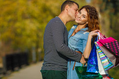 Young couple with shopping bags in the park in autumn. Stock Photography