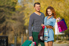 Young couple with shopping bags in the park in autumn. Stock Images