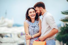 Young couple with shopping bags walking by the harbor of a touristic sea resort with boats on background. Happy young couple with shopping bags walking by the stock image