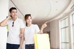 Young couple with shopping bags walking in mall royalty free stock photography