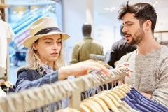 Young couple shopping for clothes. Young couple while shopping for clothes in fashion shop retail royalty free stock photo