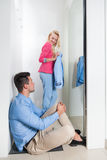 Young Couple Shopping Fitting Room Fashion Shop, Happy Smiling Girl Trying New Clothes, Man Tired Sit On Floor Bored Royalty Free Stock Photos