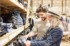Young couple shopping in front of jeans selection. Young couple shopping in front of the jeans selection in fashion shop in shopping mall stock photos