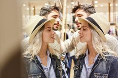 Young couple shopping in front of the mirror. Young couple shopping for clothes in the fashion shop in front of the mirror royalty free stock photos