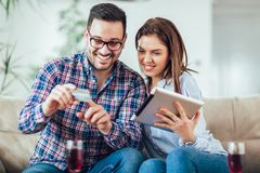 Couple shopping on internet with tablet. Young couple shopping on internet with tablet royalty free stock photos