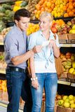 Young couple with shopping list against the heaps of fruits Stock Photography