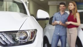 Young couple shopping for a new automobile at the delership saon. Selective focus on a car light copy space. Young happy couple choosing a new car at the stock images