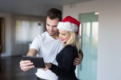 Young couple shopping online for Christmas by tablet at home. Women in santa hat ordering gift royalty free stock photo