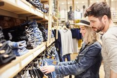 Young couple in jeans fashion shop while shopping. Young couple shopping at retail looking for jeans in fashion store stock images