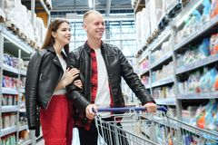 Young couple shopping in a supermarket. The men and girl looking at a product stock images