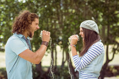 Young couple shouting through tin cans Royalty Free Stock Photo