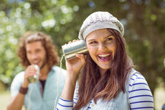 Young couple shouting through tin cans. On a summers day Royalty Free Stock Photography