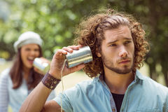 Young couple shouting through tin cans. On a summers day Stock Image
