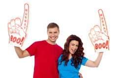 Young couple showing boo hurray foam hand. To camera, excited couple Stock Photography