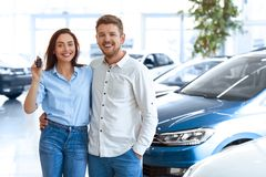 Young couple showing a key from their new car royalty free stock photography