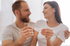 Young couple showing pregnancy test together. The happiest moment of our lives. We have Selective focus on a pregnancy test in hands of a newly married couple Royalty Free Stock Photos