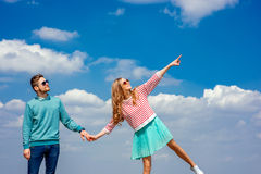 Young couple showing something on the blue cloudy sky Royalty Free Stock Photos