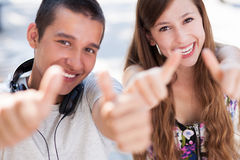 Young couple showing thumbs up. Portrait of young couple outdoors Stock Image