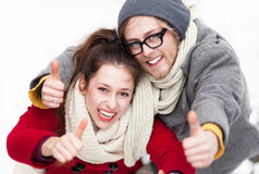 Young couple showing thumbs up. Young Couple in Winter Clothes Royalty Free Stock Image