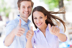 Young couple showing thumbs up. Outdoors Royalty Free Stock Photo