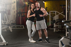 Young Couple Showing Thumbs Up. Portrait Of A Sexy Couple In The Gym With Exercise Equipment Showing Thumbs Up Royalty Free Stock Photography