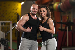 Young Couple Showing Thumbs Up. Portrait Of A Sexy Couple In The Gym With Exercise Equipment Showing Thumbs Up Stock Photo