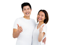 Young couple showing thumbs up. Portrait of young couple showing thumbs up on white background Stock Images
