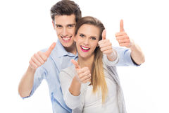 Young couple showing thumbs up. Young couple standing on white background Stock Image
