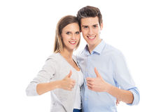 Young couple showing thumbs up. Young couple standing on white background Stock Photos