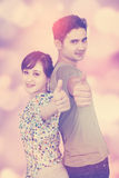 Young couple shows thumbs up. Attractive young couple smiling on the camera while showing thumbs up, shot with bokeh background Stock Image