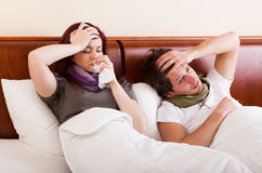 Young couple sick in bed. Young couople with flu lying in bed and treating Stock Image