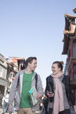 Young couple sightseeing, holding map and mobile phone. Stock Photos