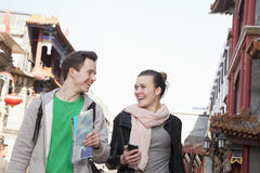 Young couple sightseeing, holding map and mobile phone. Royalty Free Stock Photos