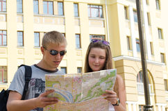 Young couple sightseeing on vacation. Low angle view of an attractive young couple sightseeing on vacation consulting a map for directions Stock Photo