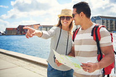 Young couple sightseeing on vacation. Standing holding a map on a waterfront promenade with an excited young women pointing to something Stock Image