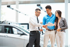 Young Couple Signing a Contract in Car Showroom. Royalty Free Stock Images