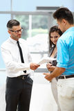 Young Couple Signing a Contract  in Car Showroom. Royalty Free Stock Photo