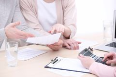 Young couple signing contract at insurance agency stock photography