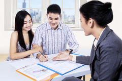 Young couple signing financial contract. Young couple signing for financial contract with businesswoman Royalty Free Stock Photography