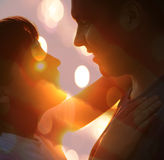 Young couple silhouette. Hugging and looking at each other outdoors at night neon city background Stock Image