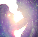 Young couple silhouette. Hugging and looking at each other outdoors at night neon city background Stock Photos
