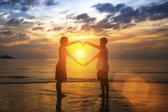 Young couple silhouette holding hands in heart shape on the beach Stock Image
