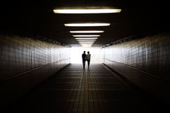 Young couple in silhouette walking towards exit of pedestrian underpass Royalty Free Stock Photography